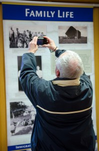 Visitor taking a photo of a display panel in the exhibit.