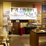 "An image of the ""People on the Move"" exhibit showing the title banner, display cases and suitcases."