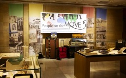 """An image of the """"People on the Move"""" exhibit showing the title banner, display cases and suitcases."""