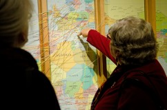 """People using the map in the """"People on the Move"""" exhibit to mark the journey of their families."""