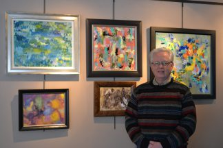 Artist Ron Duffy with paintings from the Brushed Back to Life series.