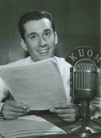 Unidentified man with KUOM microphone. University of Minnesota Radio and Television Broadcasting records, University Archives