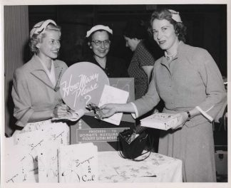 Volunteers from the Mount Sinai Hospital Women's Auxiliary sell their cookbook at a fundraising event, circa 1955
