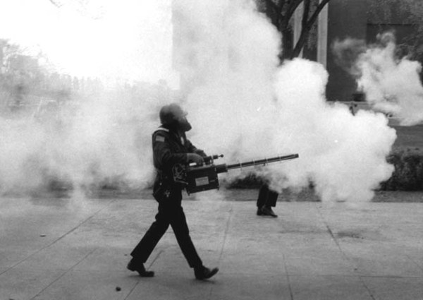 Police wearing gas masks walk through campus, attempting to disperse the crowds. University of Minnesota Archives Photograph Collection. Available at http://purl.umn.edu/71641