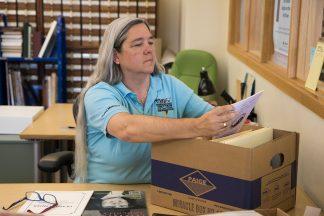 Lisa Vecoli looking through a box of materials