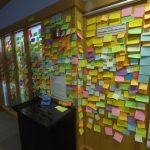 A wall covered in Post-It Notes with comments from exhibit viewers.