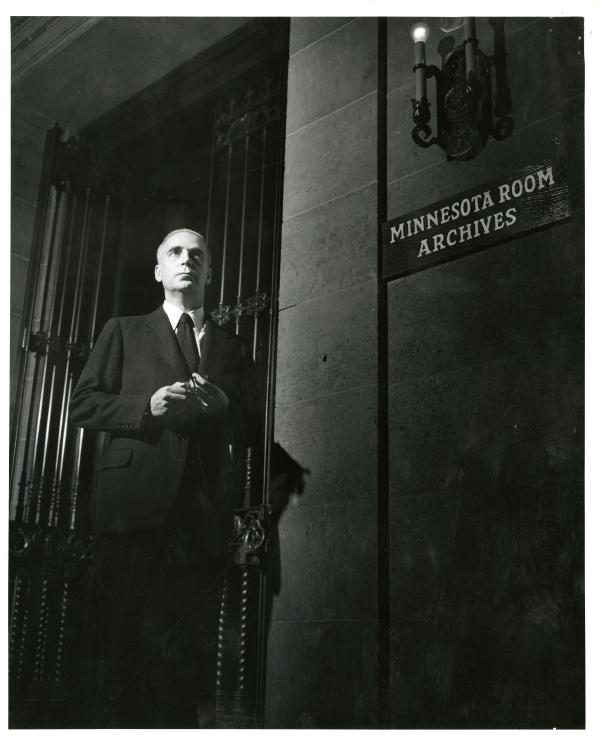 James Gray, History department faculty member and author of the 1951 centennial history of the University of Minnesota outside the archives room in Walter Library, 1949.