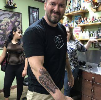 Jason Herbert with turtle tattoo on forearm
