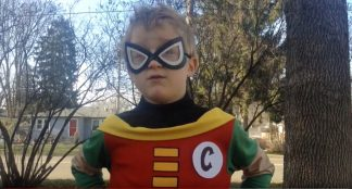 Video still of child posing as Captain Celery, standing outdoors