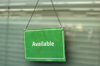 "Green sign with ""available"" printed on it hanging from the door of the 1:Button Studio."
