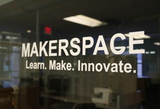 """Image of the Makerspace sign that is on the window next to the Makerspace entrance. White text states """"Makerspace"""" on top with """"Learn. Make. Innovate."""" underneath. Background is dark because lights are off in the Makerspace."""