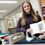 Bridget McKenna in the Wangensteen Library, holding a book on historic infant feeding.