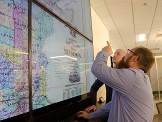 Ryan Mattke, Map & Geospatial Information Librarian, points out details on an 1871 map of Minnesota to Benjamin Wiggins, Program Director of the Digital Arts, Sciences, & Humanities (DASH) program.