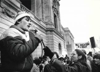 Black and white photo shows a crowd of student protestors holding signs to support the former General College. A protestor in the foreground speaks into a microphone to address the group.