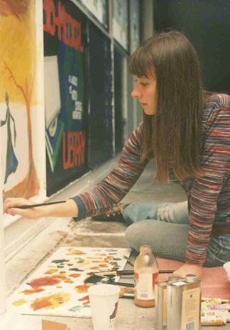 Student paints the bridge next to the panel for the Bio-Medical Library. Image circa 1990s courtesy of the University Archives.
