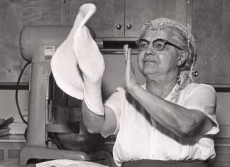 A woman tosses pizza dough with her hands. Image from the Immigration History Research Center Archives.