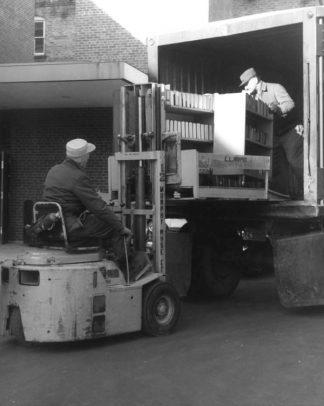 Black and white photo of movers using a fork lift to remove books from a truck.