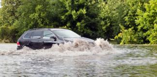 Photo of car driving through flood water.