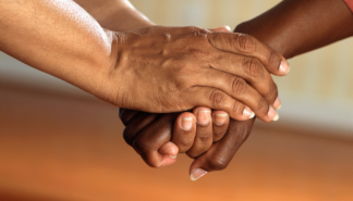 Photo of two people holding hands to depict caregiving.
