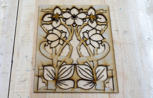 Finished laser cut of a floral design in wood.