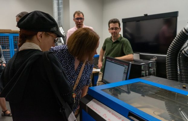 Library staff viewing laser cut in progress.