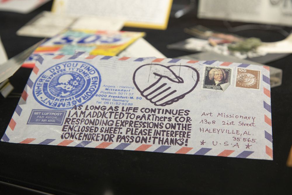 Mail art from the Stamped and Posted exhibit reads, As long as life continues I am addicted to partners' corresponding expression of the enclosed sheet. Please interfere once more or pass on. Thanks!