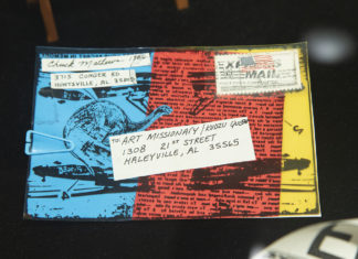 Mail art from the Stamped and Posted exhibit features a colorful background with text and line art.