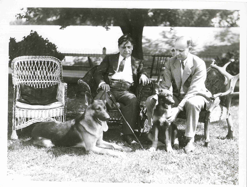 A photo from the Upper Midwest Jewish Archives shows two people sitting outdoors with two German Shepherd Dogs.