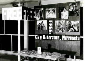 Historical photo of a table with pamphlets and a sign behind it that says FREE: Gay Liberation, Minnesota
