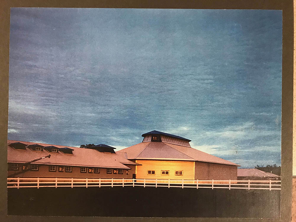 Photo of a stable and corral under a cloudy sky from the Northwest Architectural Archives.