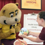 Goldy Gopher inspects a model human skull at the UMN Health Sciences Library's booth.