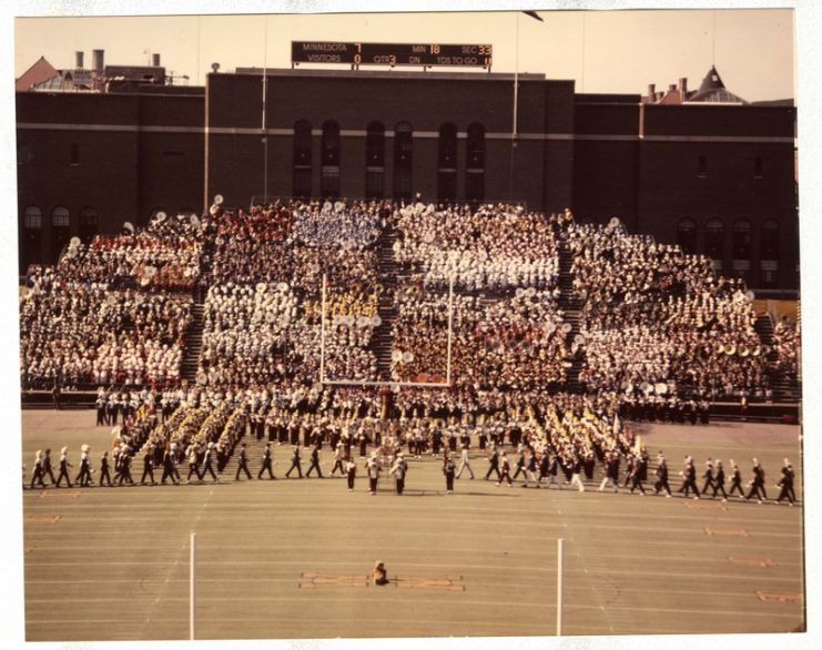 "High School Band Day with University Marching Band in block ""M"" formation, 1975, available at http://brickhouse.lib.umn.edu/items/show/46 (And who is that at the 50-yard line enjoying the performance?)"