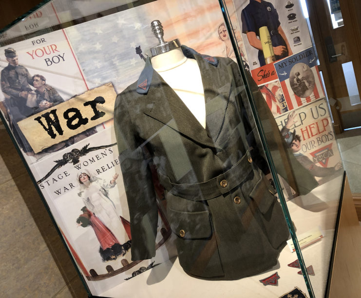 Exhibit vitrine with a YMCA women's uniform on a bust and war posters in the background