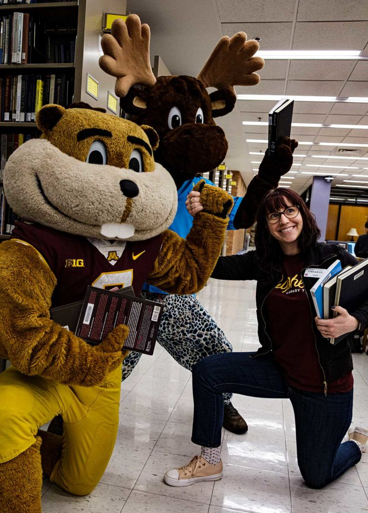 Lacie McMillan from the Libraries helps Goldy and Mooster find their books at Gopherbaloo