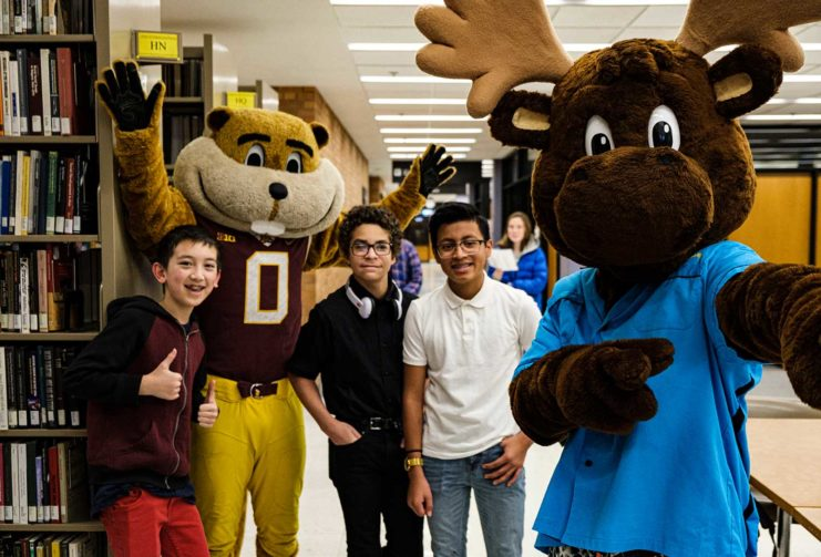 Goldy and Mooster pose with three Gopherbaloo students