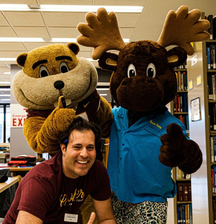 The Libraries' Phil Dudas poses with Goldy and Mooster at Gopherbaloo
