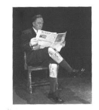 Man wearing prosthetic legs reading newspaper.