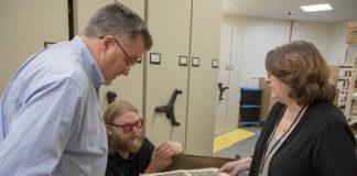 "J. B. Shank, Luke Freeman, and Maggie Ragnow examine the latest acquisition of ""Ceremonies."""
