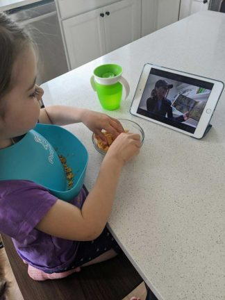 A young child watches virtual StoryTime on a tablet.