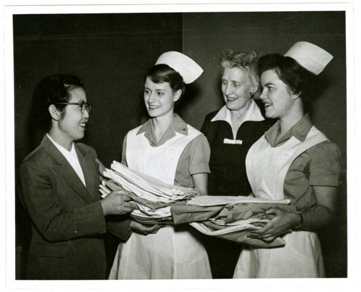 This photograph features Director Katharine J. Densford of the University of Minnesota's School of Nursing with Patricia Jaeger, President of the College Board of Nurses' Dormitory and Marily Nelson, Vice president of the Student's Nurses' Association, presenting Mrs. Kwi Hyang Lee, Principle of Seoul National University's School of Nursing with uniforms given to her Korean colleagues who are studying in the Nursing program at the University of Minnesota, in 1957. Mrs. Kwi Hyang Lee was one of the professionals from SNU who stayed in Minnesota for six months during which she was educated on nursing procedures and instructions, in which she could then apply at SNU. Source: University of Minnesota Archives, Photograph Collection.