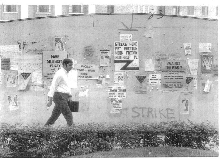 A man walks past posters and fliers anti-war messages and support for the student strike on campus. Bill Tilton papers, University Archives, University of Minnesota, Twin Cities.