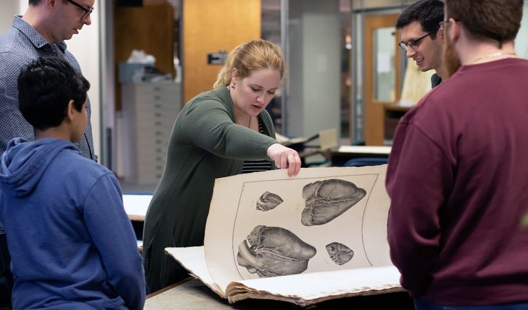 Students looking at oversized rare book.