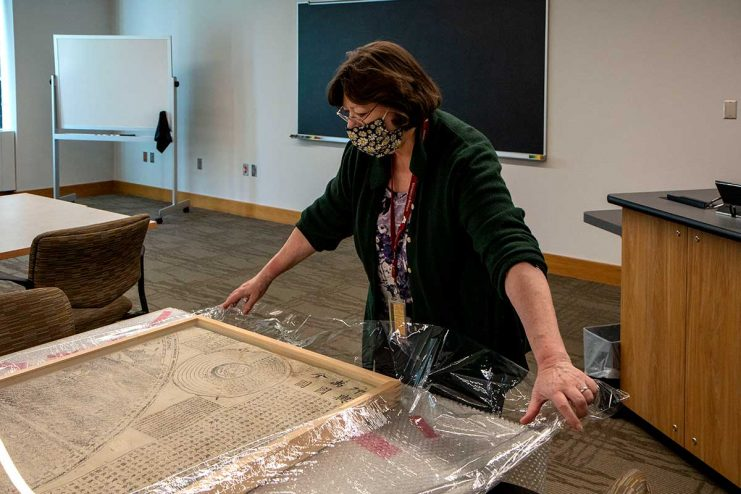Maggie Ragnow unwraps one of the six panels that make up the Ricci Map