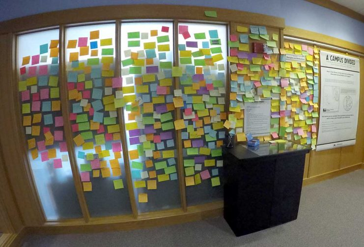 Post-it Notes on the wall commenting on the Campus Divided Exhibit