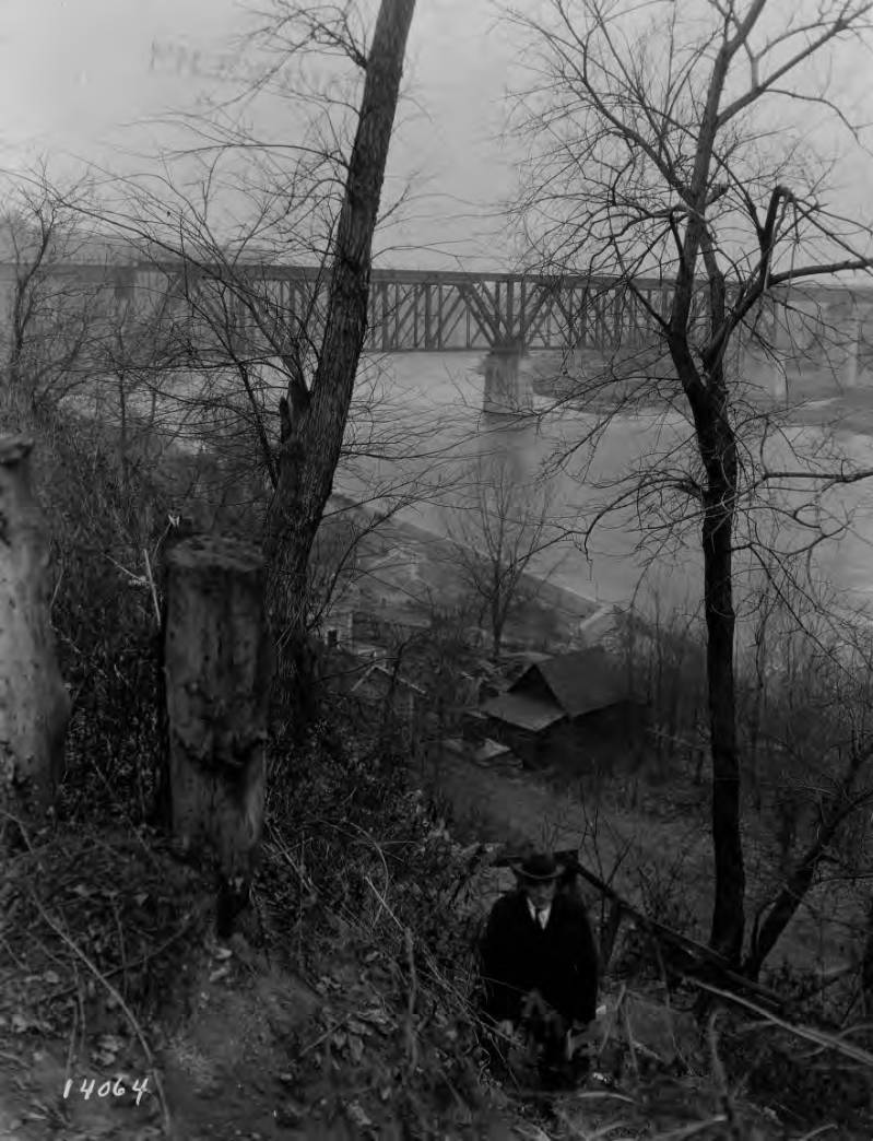 A man in a suit is walking toward the camera up from the steep bluff along the Mississippi River. At the bottom of the bluff is a wooden house and in the distance is the original Washington Ave bridge.