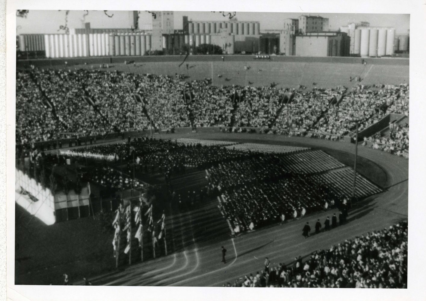 Graduates sit in chairs on the field of Memorial Stadium in front of a stage. Attendees are in the stadium bleachers.