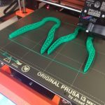 Two green tong devices are shown being printed by a 3D printer