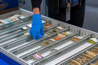 Anna Shepherd's blue-gloved hand is seen placing pharmaaceutical boxes in a large metal tray.