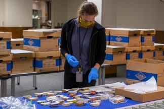 Conservation specialist Anna Shepherd is wearing a mask and gloves as she matches up pharmaceutical boxes with their corresponding bar codes.