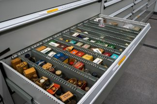 A metal drawer full of brightly colored boxes of pharmaceutical products is pulled out for viewing.